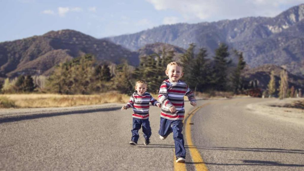 2 toddler boys running on a road