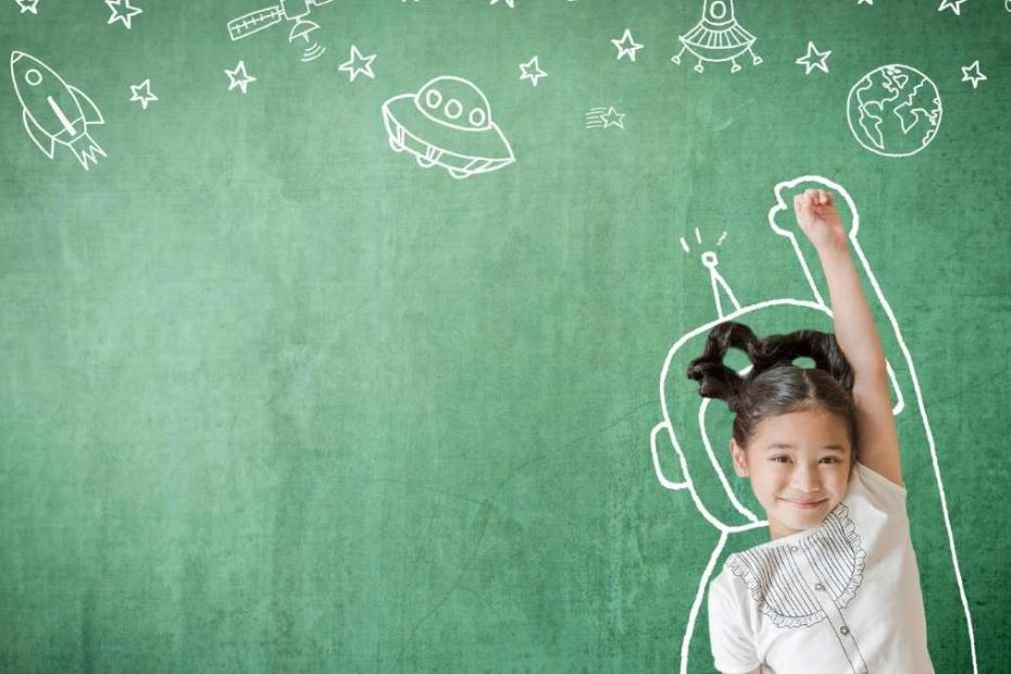 girl in front of blackboard at school with fist in the air