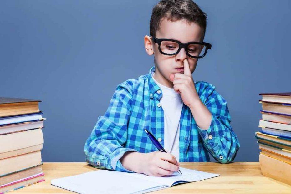 child picking nose on desk