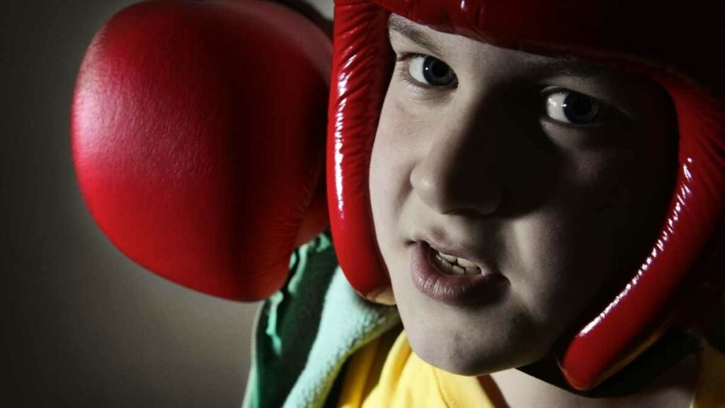 child with boxing glove punching