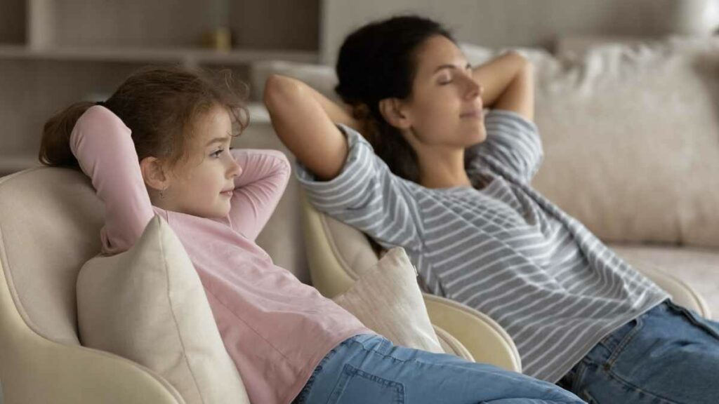 mom and daughter relaxing on sofa