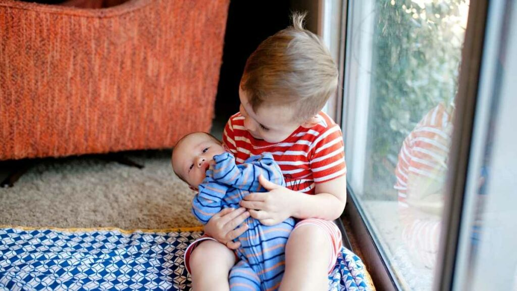 sibling helping with newborn