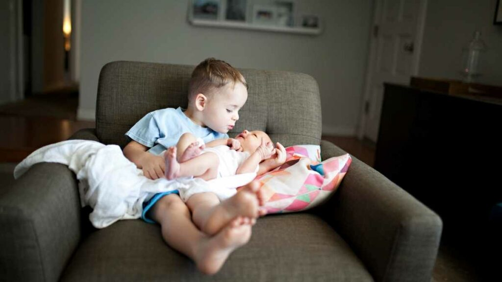 sibling helping with newborn on couch